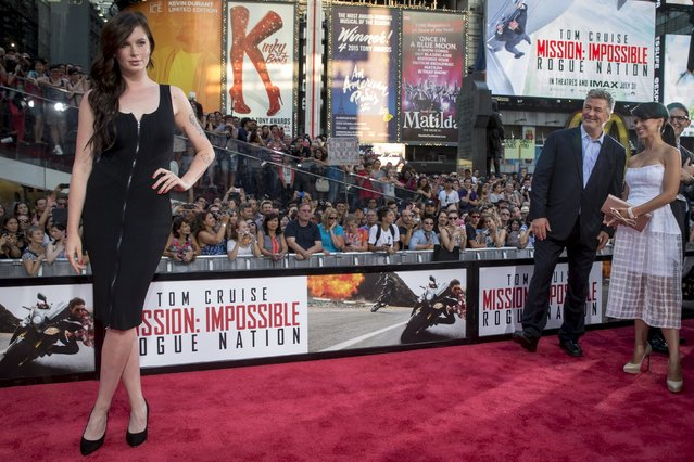 """Actor Alec Baldwin and his wife Hilaria Baldwin ( R) watch as Ireland Baldwin (L) poses on the red carpet for a screening of the film """"Mission Impossible: Rogue Nation"""" in New York July 27, 2015. (Photo by Brendan McDermid/Reuters)"""