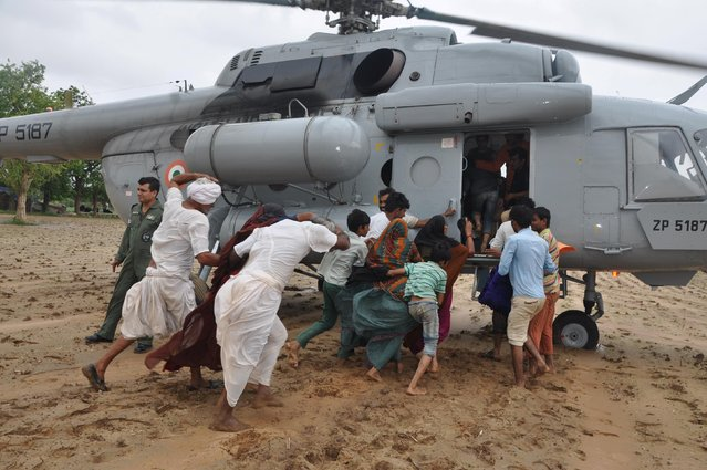 Flood-affected villagers rush to board an Indian Air Force (IAF) helicopter in Gujarat, India, July 29, 2015. At least 26 people have been killed in the flood-like situation caused by torrential monsoon rains in some parts of the western Indian state of Gujarat, local media reported on Thursday. (Photo by Reuters/India's Ministry of Defence)