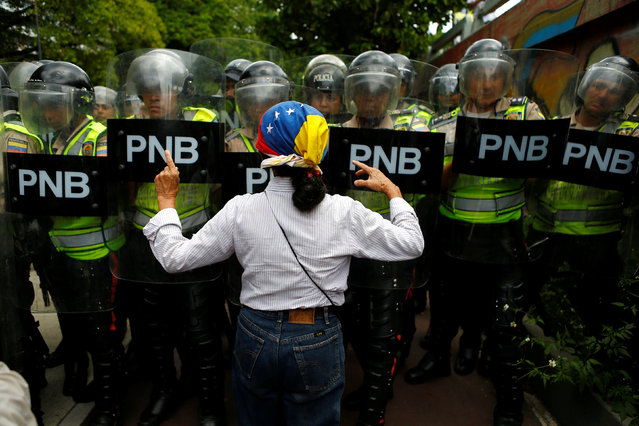 An opposition supporter argues with riot policemen during a rally to demand a referendum to remove President Nicolas Maduro in Caracas, Venezuela, June 7, 2016. (Photo by Ivan Alvarado/Reuters)