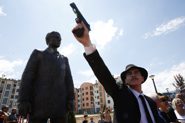 Bosnian actor Jovan Mojsilovic poses with a plastic replica gun  during ceremony of unveiling statue of Gavrilo Princip in Istocno Sarajevo, on Friday, June 27, 2014. Marking the centennial of the beginning of World War I in their own way, Bosnian Serbs have unveiled a monument of Gavrilo Princip in the Eastern part of Sarajevo to the man who ignited the war by assassinating the Austro-Hungarian crown prince on June 28, 1914. (Photo by Amel Emric/AP Photo)