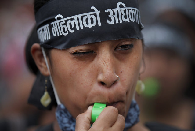 A Nepalese women blows on a whistle during a protest demanding provision in the new constitution to avail citizenship in the name of one's mother, in Kathmandu, Nepal, Tuesday, August 4, 2015. Nepal's proposed new constitution has sparked fury from women who protested against the denial of citizenship rights to children if their fathers are not Nepalese citizens. (Photo by Niranjan Shrestha/AP Photo)