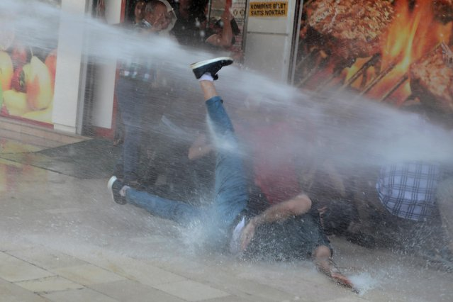 Turkish police use a water cannon to disperse demonstrators during a protest against the replacement of Kurdish mayors with state officials in three cities, in Diyarbakir, Turkey, August 19, 2019. Riot police fired water cannon and tear gas to disperse protesters demonstrating in southeast Turkey on Tuesday against the ousting of three Kurdish mayors five months after they were elected. (Photo by Sertac Kayar/Reuters)