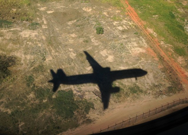 """A TAM passenger jet casts a shadow on the ground as it descends to land in Sao Paulo June 30, 2014. In a project called """"On The Sidelines"""" Reuters photographers share pictures showing their own quirky and creative view of the 2014 World Cup in Brazil. (Photo by Mike Blake/Reuters)"""