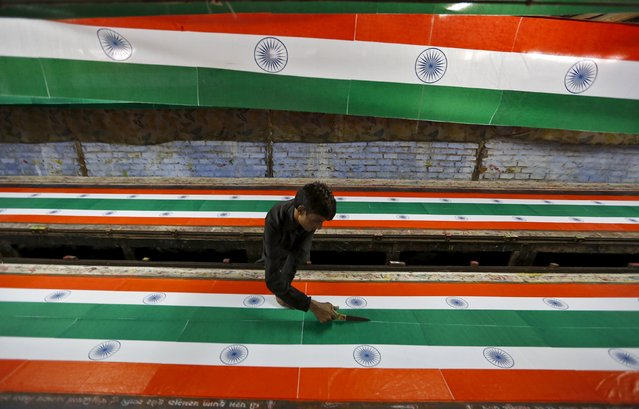 A worker uses a pair of scissors as he makes Indian national flags inside a textile printing workshop ahead of the Independence Day celebrations in Ahmedabad, India, August 10, 2015. (Photo by Amit Dave/Reuters)