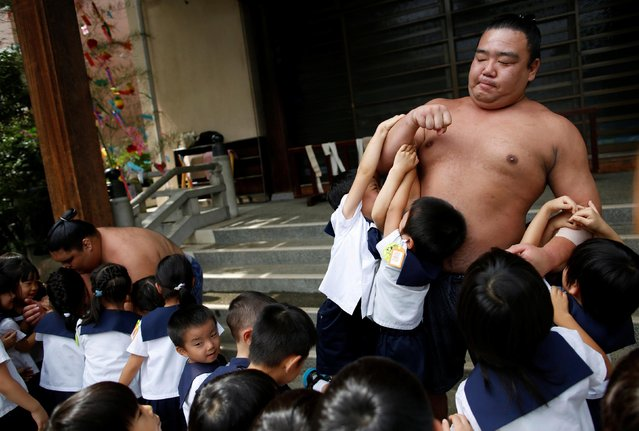 Sumo wrestler Kainoryu (R) plays with kindergarten children at Ganjoji Yakushido temple in Nagoya, Japan on July 18, 2017. (Photo by Issei Kato/Reuters)