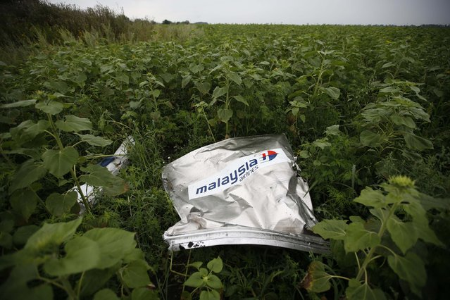 Debris from a Malaysian Airlines Boeing 777 that crashed on Thursday lies on the ground near the village of Rozsypne in the Donetsk region July 18, 2014. World leaders demanded an international investigation into the shooting down of Malaysia Airlines Flight MH17 with 298 people on board over eastern Ukraine in a tragedy that could mark a pivotal moment in the worst crisis between Russia and the West since the Cold War. (Photo by Maxim Zmeyev/Reuters)