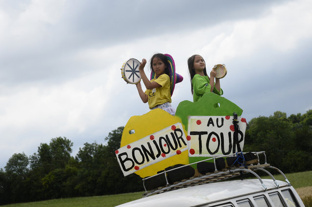 "Girls play music behind placards reading ""Hello Tour de France"" during the 161 km eighth stage of the 101st edition of the Tour de France cycling race on July 12, 2014 between Tomblaine and Gerardmer La Mauselaine, eastern France. (Photo by Lionel Bonaventure/AFP Photo)"