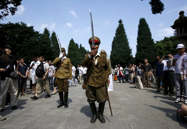 Men dressed as Japanese imperial army soldiers present arms at Yasukuni Shrine in Tokyo August 15, 2015, to mark the 70th anniversary of Japan's surrender in World War Two. Japanese Prime Minister Shinzo Abe sent an offering to a shrine for war dead on Saturday, the 70th anniversary of Japan's World War Two defeat, but did not visit the shrine, seen in China and South Korea as a symbol of Tokyo's wartime militarism. (Photo by Issei Kato/Reuters)