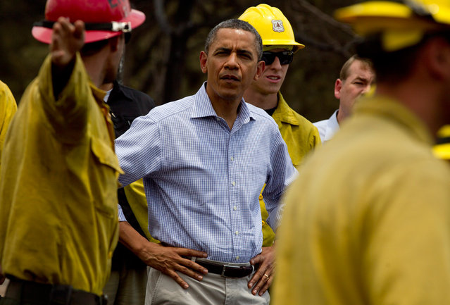 """President Barack Obama talks with firefighters as he tours the Mountain Shadow neighborhood devastated by a wildfire in Colorado Springs, on June 29, 2012. After declaring a """"major disaster"""" in the state early Friday and promising federal aid, President Obama got a firsthand view of the wildfires and their toll on residential communities. (AP Photo/Carolyn Kaster)"""