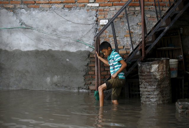 A boy holds onto a stair railing as he walks in floodwaters flowing from the swollen Bagmati River brought on by heavy rainfall in Kathmandu, Nepal August 17, 2015. (Photo by Navesh Chitrakar/Reuters)