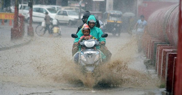 Indian commuters ride on a scooter during a spell of monsoon showers in Bhopal, India, 03 July 2016. The summer monsoon season in India usually begins in the months of June and July and lasts until October. (Photo by Sanjeev Gupta/EPA)