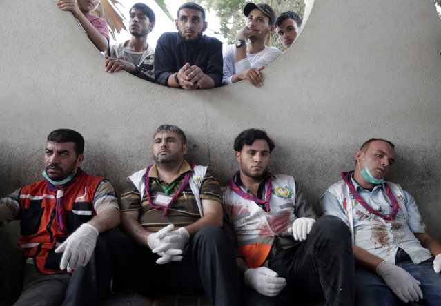Palestinian medics take a break after carrying wounded people injured from an Israeli strike in Shijaiyah neighborhood, into the emergency room at Gaza City's Shifa hospital, Wednesday, July 30, 2014. (Photo by Lefteris Pitarakis/AP Photo)
