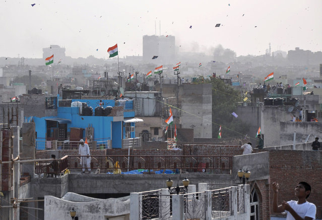 Indian youngsters fly kites on the roof top of their houses in the old quarters of Delhi to celebrate the 71 st India' s Independence Day in New Delhi on August 15, 2017. (Photo by AFP Photo/Stringer)