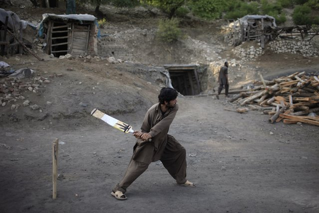 A miner plays cricket in the evening at a coal field in Choa Saidan Shah, Punjab province, May 5, 2014. (Photo by Sara Farid/Reuters)