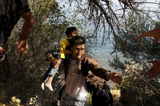 An Afghan migrant carrying a baby is helped to climb a slope moments after arriving on a dinghy on the island of Lesbos, Greece August 22, 2015. Greece ferried hundreds of refugees to its mainland on Friday to relieve the pressure on outlying islands that have been overwhelmed by thousands of people arriving by boat to flee Syria's civil war. (Photo by Alkis Konstantinidis/Reuters)