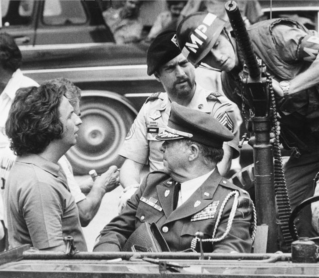 "In this September 11, 1977 file photo, director Michael Cimino, left, talks with actor Robert De Niro, center wearing beret, during a break in filming of ""The Deer Hunter"" on location in Bangkok. (Photo by Neal Ulevich/AP Photo)"