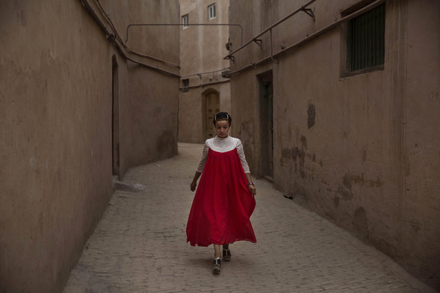 A Uyghur woman wearing a gown for the Eid holiday walks from her house on July 30, 2014 in old Kashgar, Xinjiang Province, China. (Photo by Kevin Frayer/Getty Images)