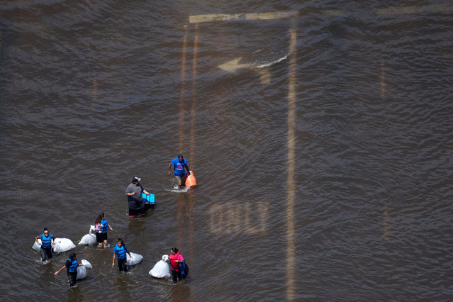 A group of people carry supplies through flood waters caused by Tropical Storm Harvey in Port Arthur, Texas, U.S. August 31, 2017. (Photo by Adrees Latif/Reuters)