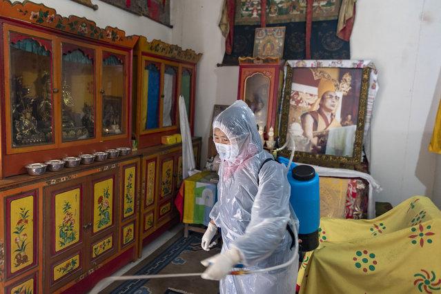 A portrait of the Tibetan spiritual leader the Dalai Lama adorns a prayer room as an employee of the Central Tibetan Administration in protective clothing sprays a steriliser as a precaution against the coronavirus in Dharmsala, India, Thursday, March 19, 2020. (Photo by Ashwini Bhatia/AP Photo)