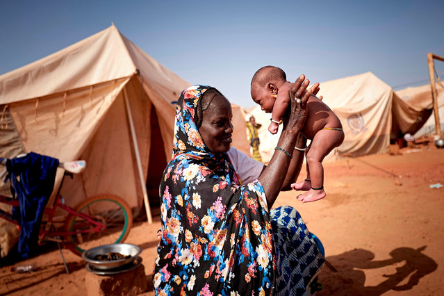 A woman plays with her baby in a camp for IDPs in Sevare on March 02, 2020. In total 151 households and 712 Internal Displaced People fled their villages in central Mali and found a shelter in the camp CAN 2002 of Sevare. (Photo by Michele Cattani/AFP Photo)