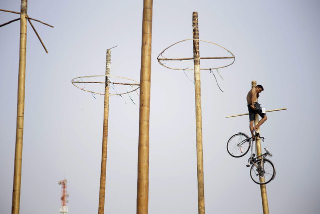 A participant uses his feet to lower a bicycle down from the top of a greased-pole during a greased-pole climbing competition held as a part of the Independence Day celebrations in Jakarta, Indonesia, Sunday, August 17, 2014. (Photo by Dita Alangkara/AP Photo)