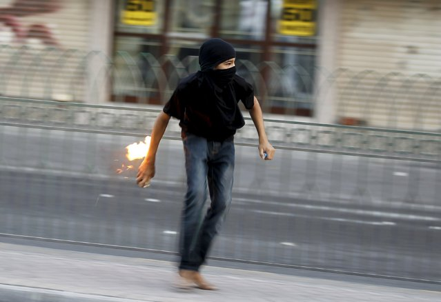 A protester runs with a molotov cocktail in his hand towards riot police during clashes after a protest in the village of Sitra south of Manama, Bahrain, August 28, 2015. Hundreds of protesters shouting anti-government slogans asking to free Al Wefaq member Hassan Isa who was arrested by authorities upon his arrival at the Bahrain International airport. (Photo by Hamad I. Mohammed/Reuters)