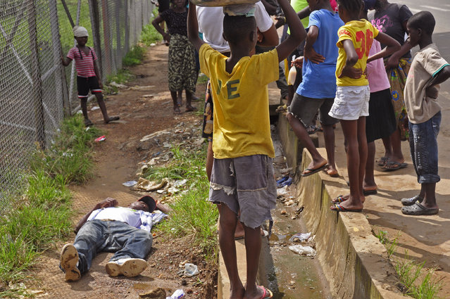 Children surround a man, left, that fell down while walking on a street suspected of having contracted the Ebola virus in the city of Monrovia, Liberia, Tuesday, August 19, 2014. The World Health Organization says the outbreak has killed more than 1,200 people, while authorities struggle to contain its spread and treat the sick. (Photo by Abbas Dulleh/AP Photo)