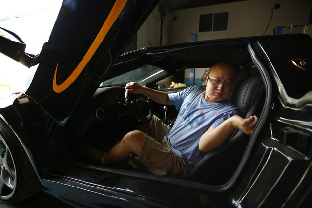 Li Lintao sits in a handmade replica of Lamborghini Diablo as he and Wang Yu (not pictured) prepare for a test drive at a garage on the outskirts of Beijing, August 21, 2014. (Photo by Petar Kujundzic/Reuters)