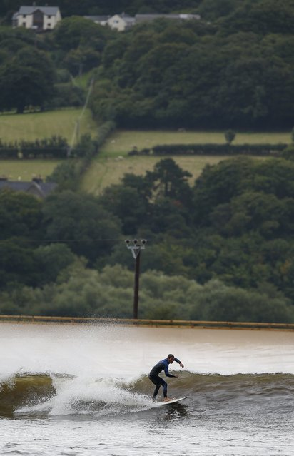 Surfers surf at Surf Snowdonia in Conwy, North Wales, September 3, 2015. (Photo by Andrew Yates/Reuters)