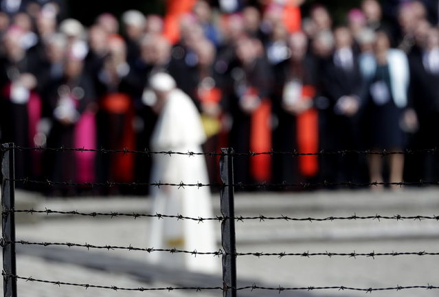 Pope Francis, background, is framed by a barbed wire as he prays in front of the Memorial at the former Nazi Death Camp Auschwitz-Birkenau, in Oswiecim, Poland, Friday, July 29, 2016. Pope Francis paid a somber visit to the Nazi German death camp of Auschwitz-Birkenau Friday, becoming the third consecutive pontiff to make the pilgrimage to the place where Adolf Hitler's forces killed more than 1 million people, most of them Jews. (Photo by Gregorio Borgia/AP Photo)