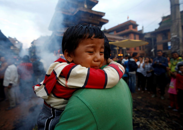 A child hugs a man as an effigy of the demon Ghantakarna is burnt, to symbolize the destruction of evil, during the Ghantakarna festival at the ancient city of Bhaktapur, Nepal August 1, 2016. (Photo by Navesh Chitrakar/Reuters)