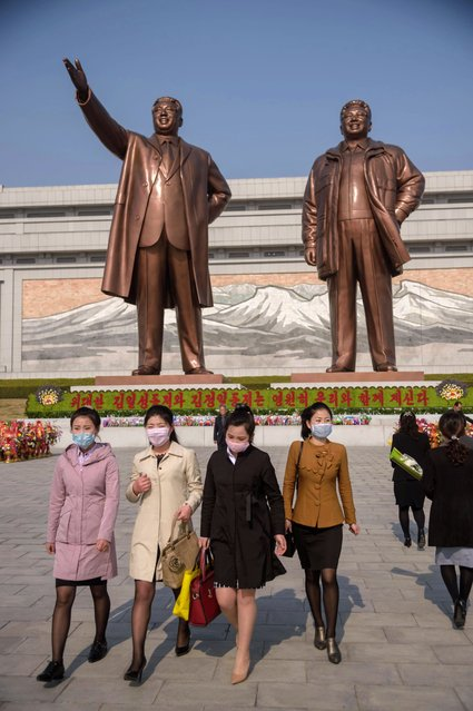 "People wearing face masks leave after laying flowers before the statues of late North Korean leaders Kim Il Sung and Kim Jong Il on the occasion of the 108th birthday of late North Korean leader Kim Il Sung, known as the ""Day of the Sun"", in Pyongyang on April 15, 2020. (Photo by Kim Won Jin/AFP Photo)"