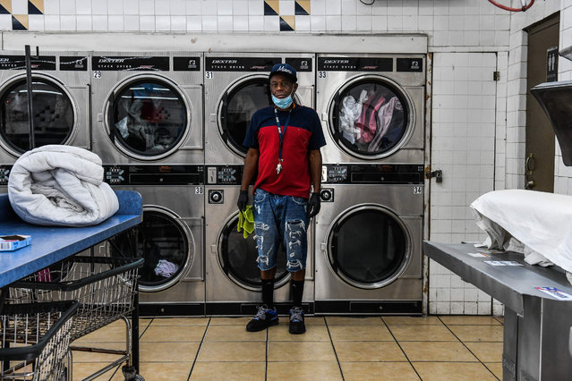 US Gregory Stark, 54, laundry shop employee poses for a picture in Miami, United States, on April 17, 2020 during the COVID-19 coronavirus pandemic. Ahead of May Day on May 1, 2020, AFP portrayed 55 workers defying the novel coronavirus around the world. Gregory Stark feels blessed for having a job and feels obligated because not everybody has a washing machine at home. He feels it's a new world, and not only him but the word that is affected by the new coronavirus. He wears facemask and gloves all day to keep him protected as he helps customers bringing in their clothes from their cars and sorting them out. (Photo by Chandan Khanna/AFP Photo)