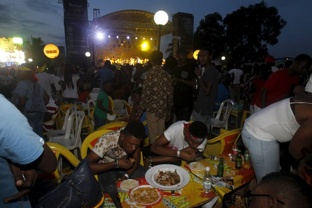 Attendees eat during the Festival des Grillades, in the yard of the Culture Palace of Abidjan, September 5, 2015. (Photo by Luc Gnago/Reuters)