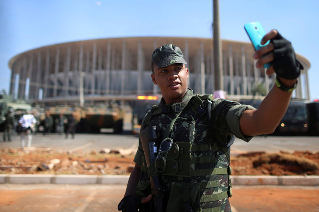 A Brazilian soldier takes a selfie outside the Mane Garrincha National Stadium, which will be one of the venues for the soccer competition of the 2016 Rio Olympic Games, during a presentation of the security scheme in Brasilia, Brazil July 22, 2016. (Photo by Adriano Machado/Reuters)