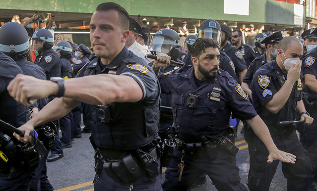 New York Police officers push back protesters during a demonstration Saturday, May 30, 2020, in the Brooklyn borough of New York. Protests were held throughout the city over the death of George Floyd, a black man who was in police custody in Minneapolis. Floyd died after being restrained by Minneapolis police officers on Memorial Day. (Photo by Seth Wenig/AP Photo)