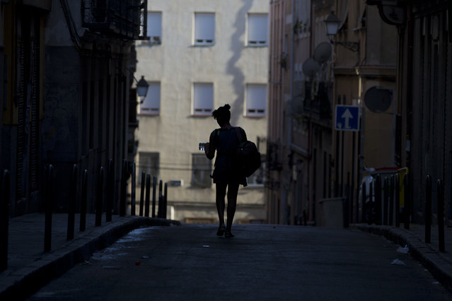 A woman walks down a narrow street with a bottle of water at the end of another hot day in Madrid, Spain, Saturday, August 13, 2016. (Photo by Paul White/AP Photo)