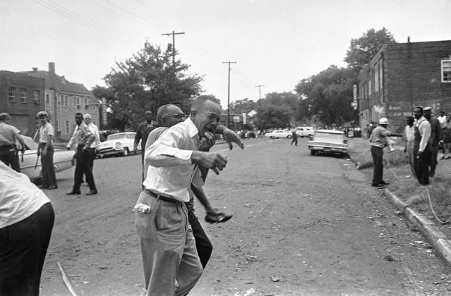 A grieving relative of one of bombing victims in Birmingham, Ala., September 15, 1963 at the Sixteenth Street Baptist Church is led away after telling officers that some of his family was in the section most heavily damaged. Man just in back of him is holding a shoe found in the debris. At least four persons were known to have been killed. (Photo by AP Photo)