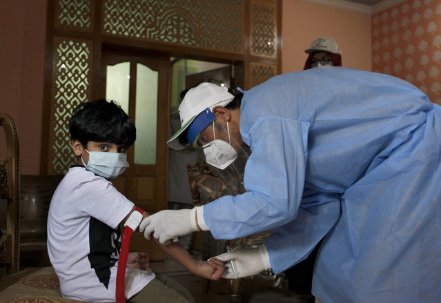 A health worker takes blood sample of a boy during door-to-door testing and screening facility for the coronavirus, Wednesday, June 10, 2020. Pakistan's coronavirus infections soared as the World Health Organization urged the government to impose a two-week lockdown to stem the relentless spike in new cases. (Photo by Anjum Naveed/AP Photo)