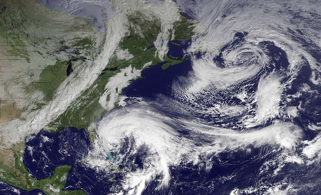 """In this image taken by NOAA's GOES East at 2:45 GMT on Friday, Hurricane Sandy is seen in the center bottom. It is expected to move north, just off the eastern seaboard. When Hurricane Sandy becomes a hybrid weather monster some call """"Frankenstorm"""" it will smack the East Coast harder and wider than last year's damaging Irene, forecasters said Friday. (Photo by NOAA)"""