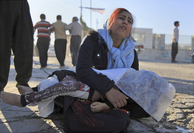 A woman mourns as she holds the body of her daughter, who died in an earthquake, in Sarpol-e-Zahab, western Iran, Monday, November 13, 2017. (Photo by Mosleh Pirkhezranian/Islamic Republic News Agency via AP Photo)