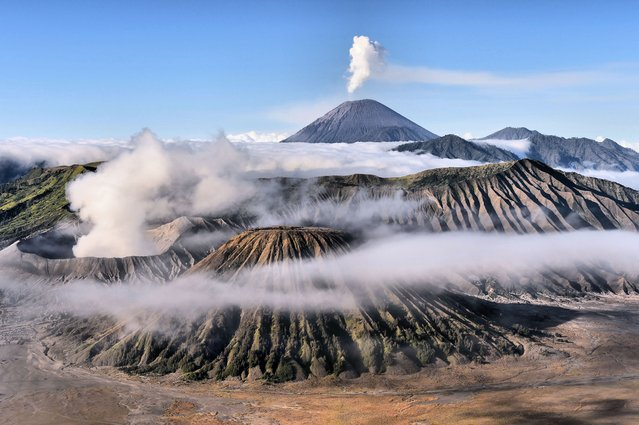 """""""Misty morning at Mount Bromo"""". Misty morning at Mount Bromo, Mount Batok and Semeru when I take this picture. I Had waited 3 hours to get this moment. Photo location: East Java. (Photo and caption by Achmad Sumawijaya/National Geographic Photo Contest)"""