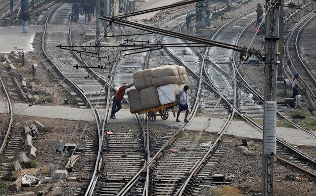 Men transport goods across railway tracks in New Delhi, India, November 16, 2017. (Photo by Saumya Khandelwal/Reuters)