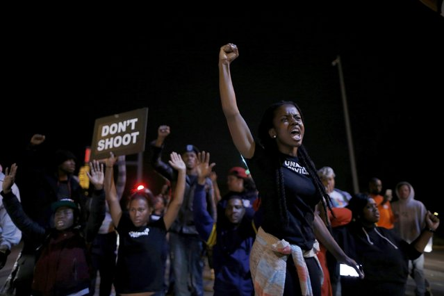 Protesters cheer after blocking an intersection after a vigil in St. Louis, Missouri, October 9, 2014. A 32-year-old white St. Louis police officer fatally shot 18-year-old Vonderrit Myers Jr. after the officer, who was off duty working for a private security company, saw Myers and two friends running and pursued them, according to a statement issued by the St. Louis police department. (Photo by Jim Young/Reuters)