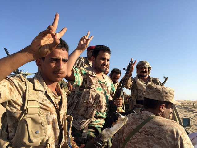 A group of soldiers trained by Emirati and Gulf Arab forces flash the victory sign near a military base in the Yemeni frontline province of Marib September 14, 2015. (Photo by Noah Browning/Reuters)