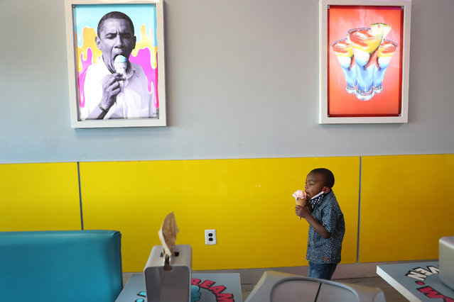 Charistan Hood, 4, eats an ice cream near a picture of former President Barack Obama at the Black-owned Ice Cream Heaven store on Blackout Day 2020 on July 07, 2020 in Miami Gardens, Florida. Supporters of Blackout Day have committed to only spending money at Black-owned businesses to showcase the economic power of the Black community. (Photo by Joe Raedle/Getty Images)