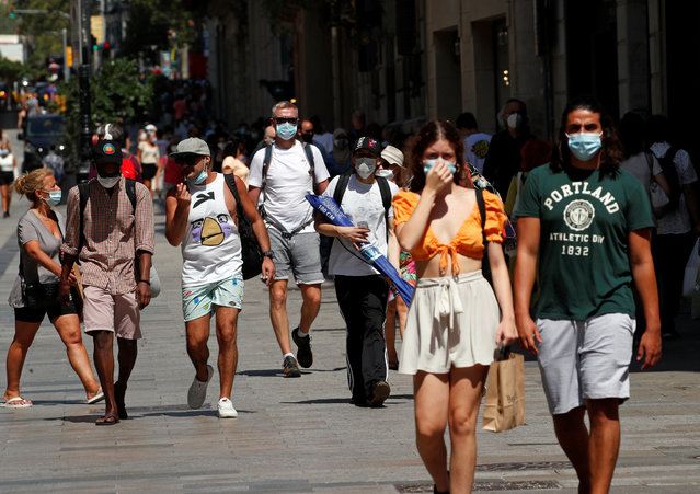 People wear protective face masks as they make their way, amid the coronavirus disease (COVID-19) outbreak, in Barcelona, Spain on July 27, 2020. (Photo by Albert Gea/Reuters)