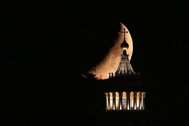 """The moon is seen behind the Saint Peter's Basilica during """"The Night of the Moon"""" in Rome, Italy, 19 September 2015. Locals and obsevers gather to view the phenomenon themmed """"Moonwatch Party"""", an international initiative launched by NASA in 2010. (Photo by Alessandro Di Meo/EPA)"""