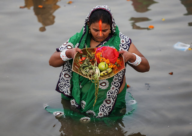 A Hindu devotee prays while standing in the waters of the Arabian Sea as she worships the Sun god Surya during the Hindu religious festival Chatt Puja in Mumbai October 29, 2014. (Photo by Shailesh Andrade/Reuters)