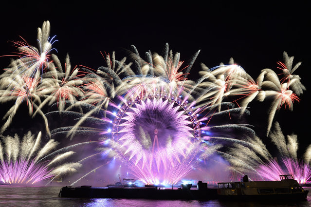 Fireworks light up the sky over the London Eye in central London during the New Year celebrations on January 1, 2018. (Photo by John Stillwell/PA Images via Getty Images)